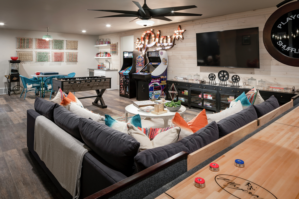 Basement with transitional ceiling fan and couch