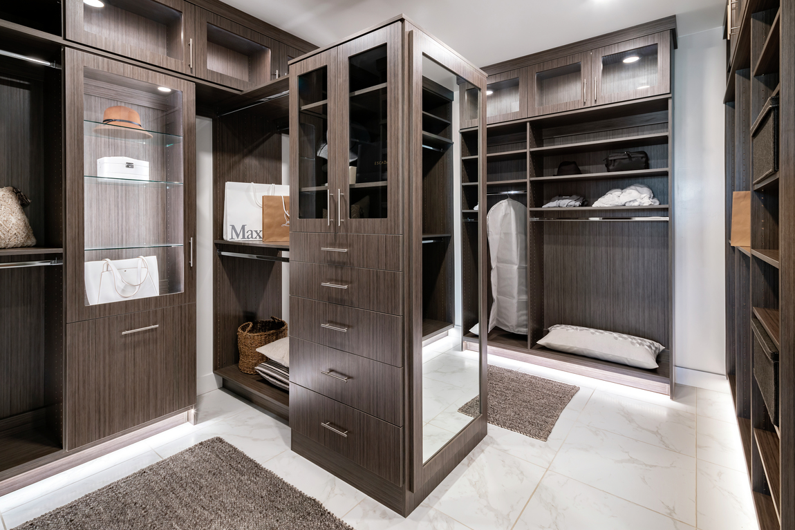 Closet with dark wood color and marbled tile floor.