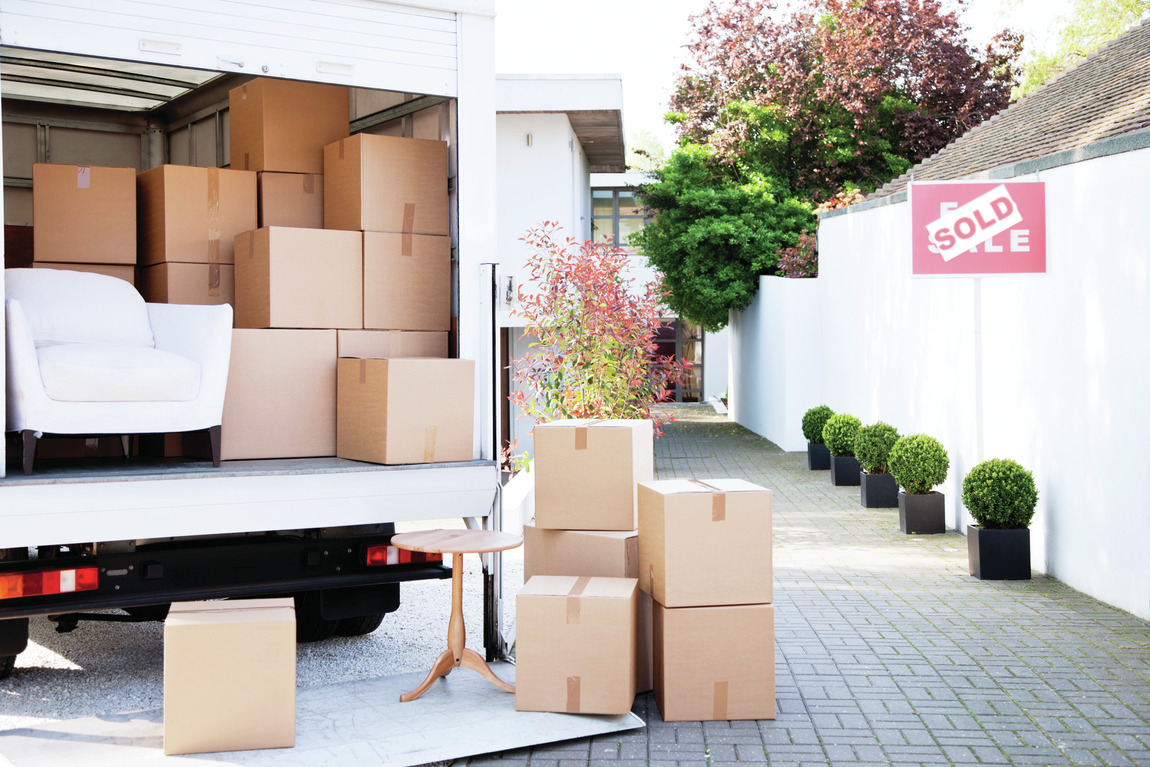 Moving truck packed with boxes outside home