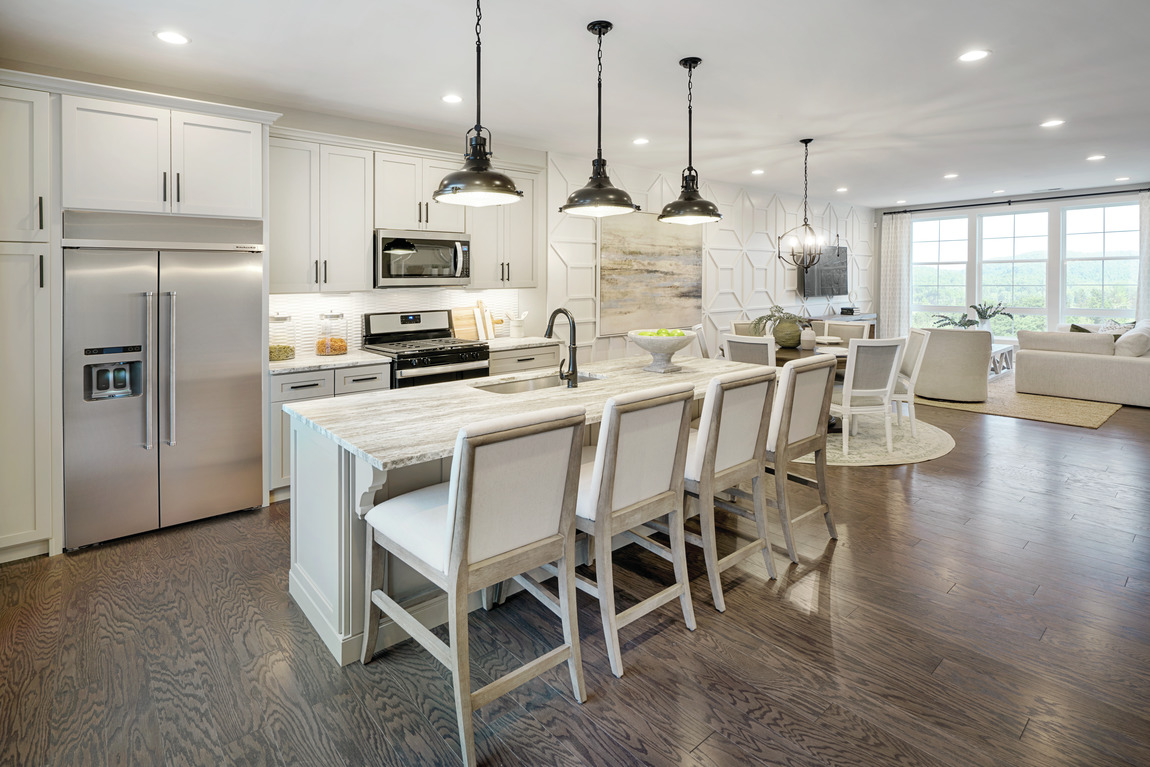 A transitional kitchen with four large barstools to match the center island.