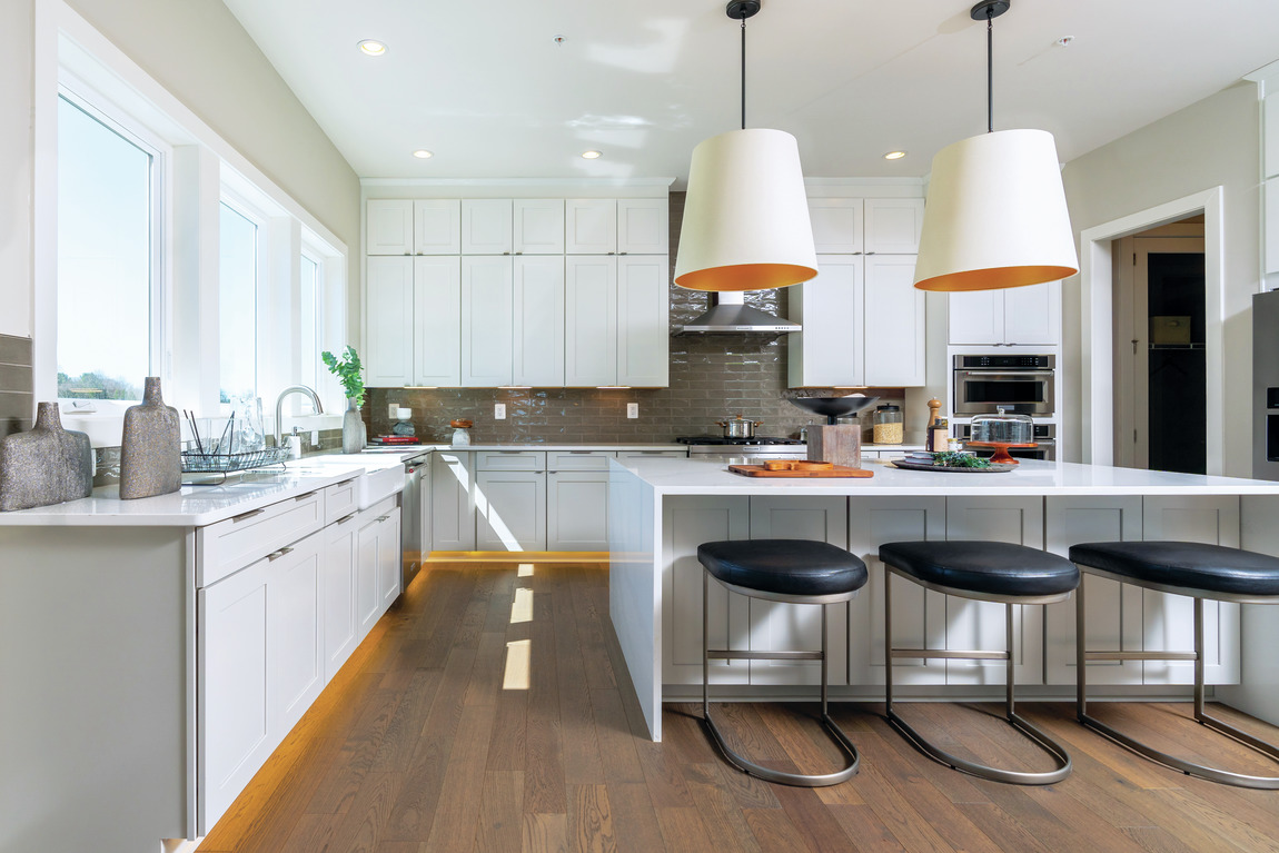 A large modern kitchen with luxury features such as a waterfall center island.