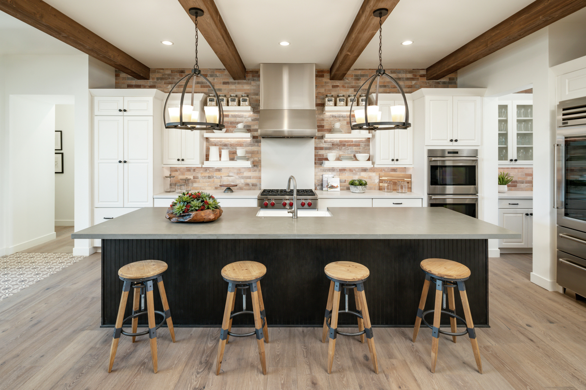 A farmhouse kitchen design with wood ceiling beams and wooden barstools along the large center island.