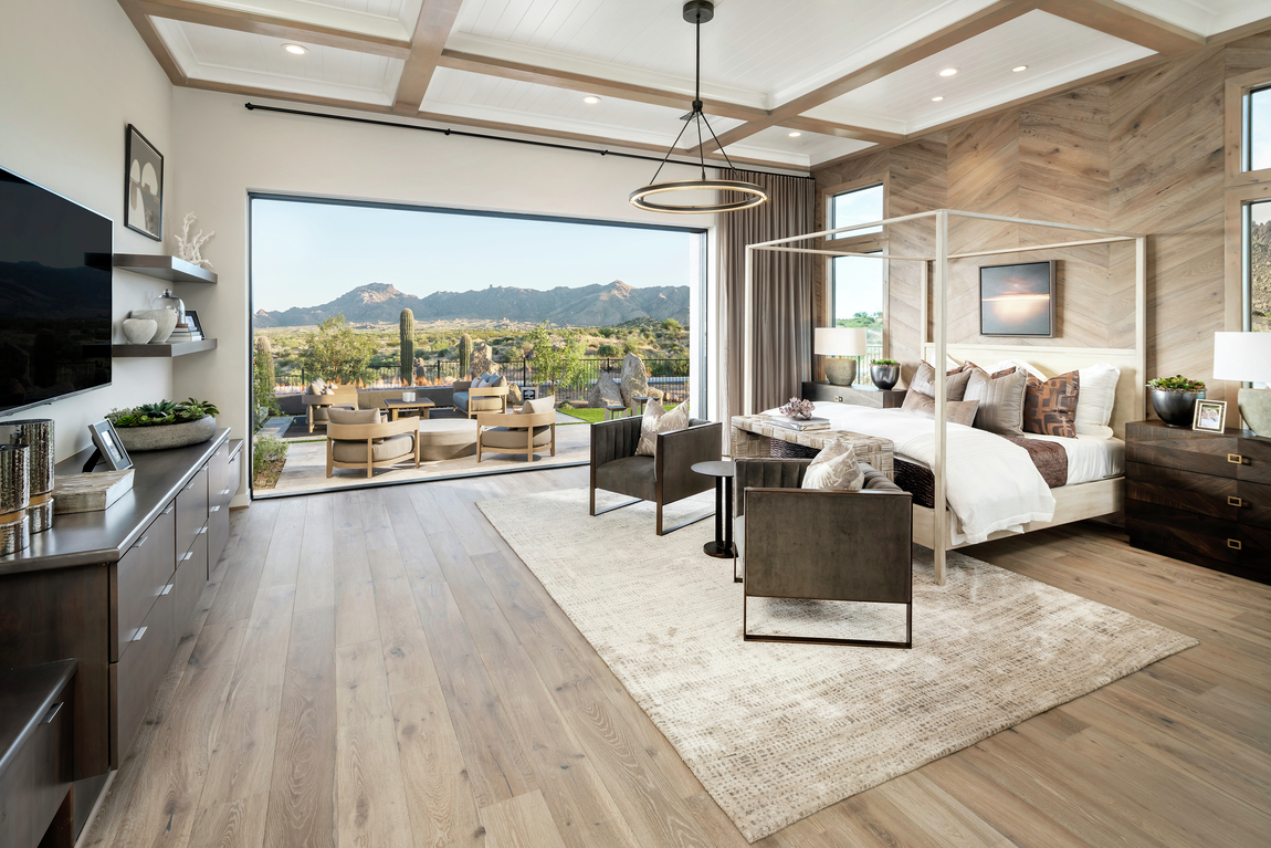 A rustic bedroom in a luxury home with sliding doors that open to a patio.