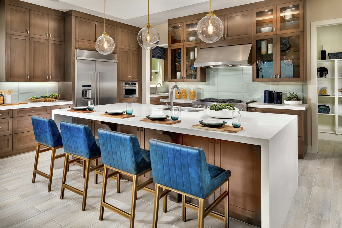 A luxurious kitchen with vibrant blue barstools along the wooden kitchen island.
