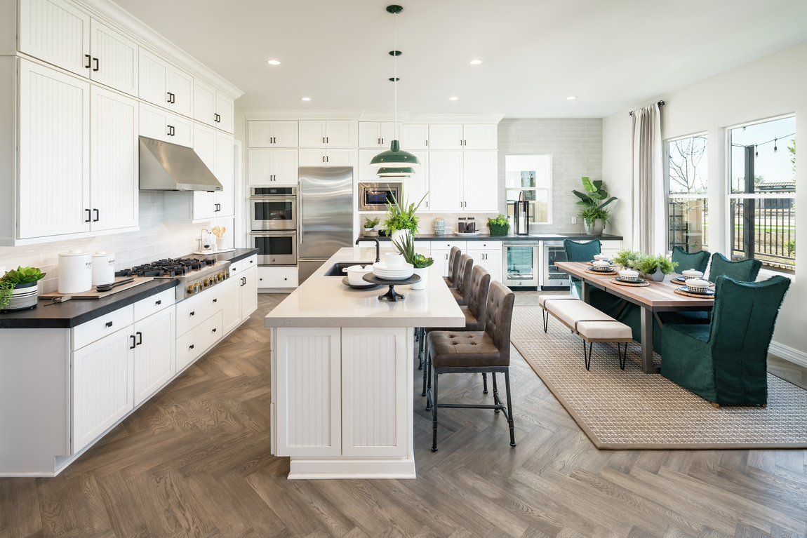 Kitchen featuring teal and green color scheme and large leather barstools.