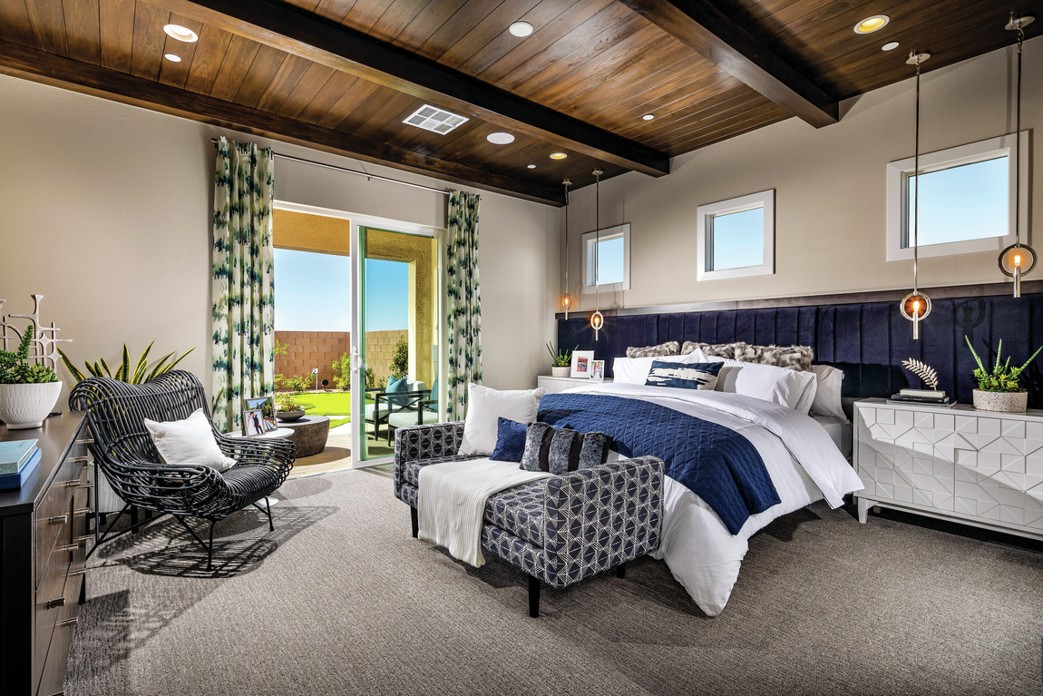 A contemporary bedroom with blue accents and comfortable furniture.