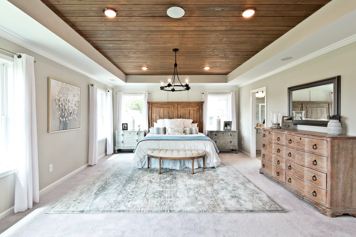 A large primary bedroom with a country style design and a wooden ceiling.