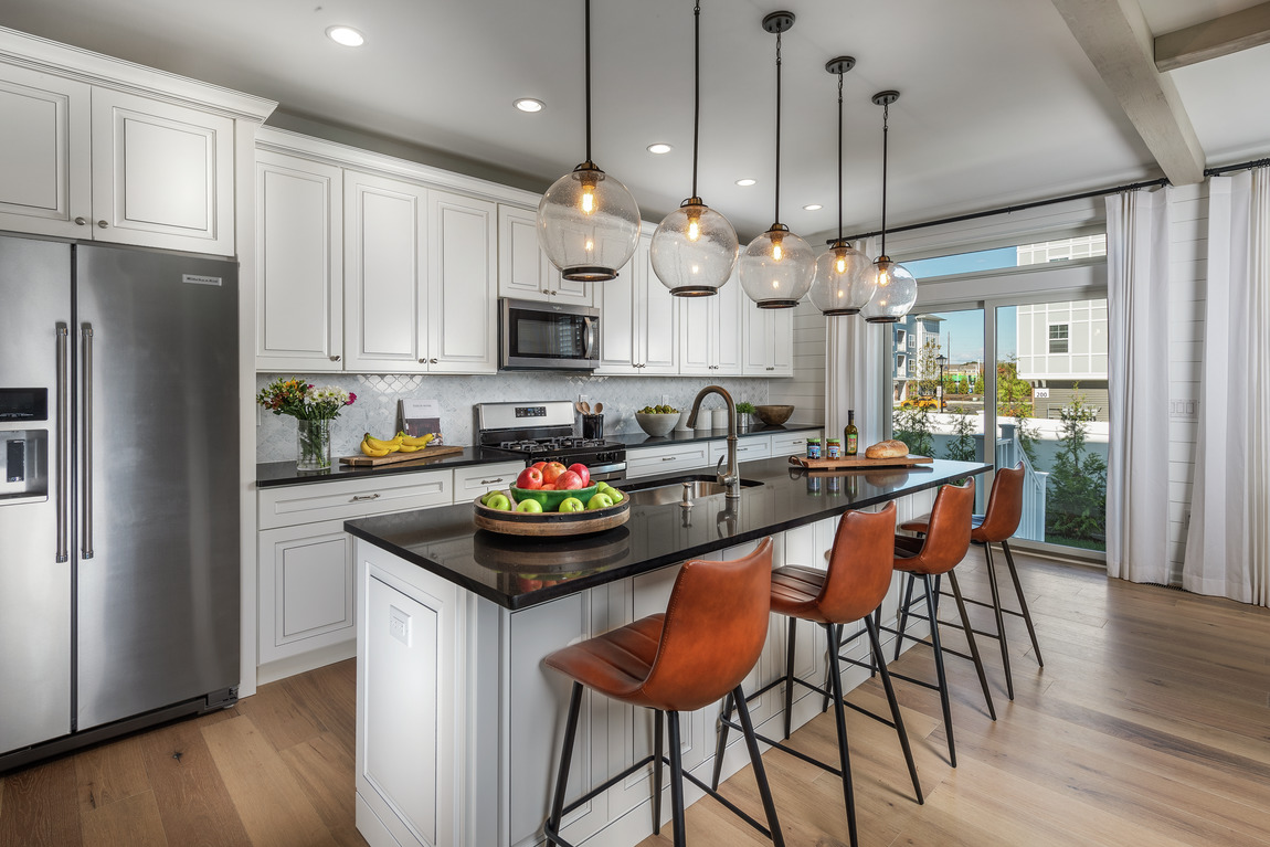 Modern farmhouse kitchen with industrial lighting and seating for four at the center island.