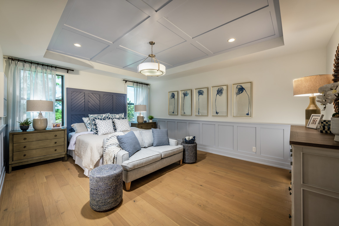 A primary bedroom with an accent ceiling design.