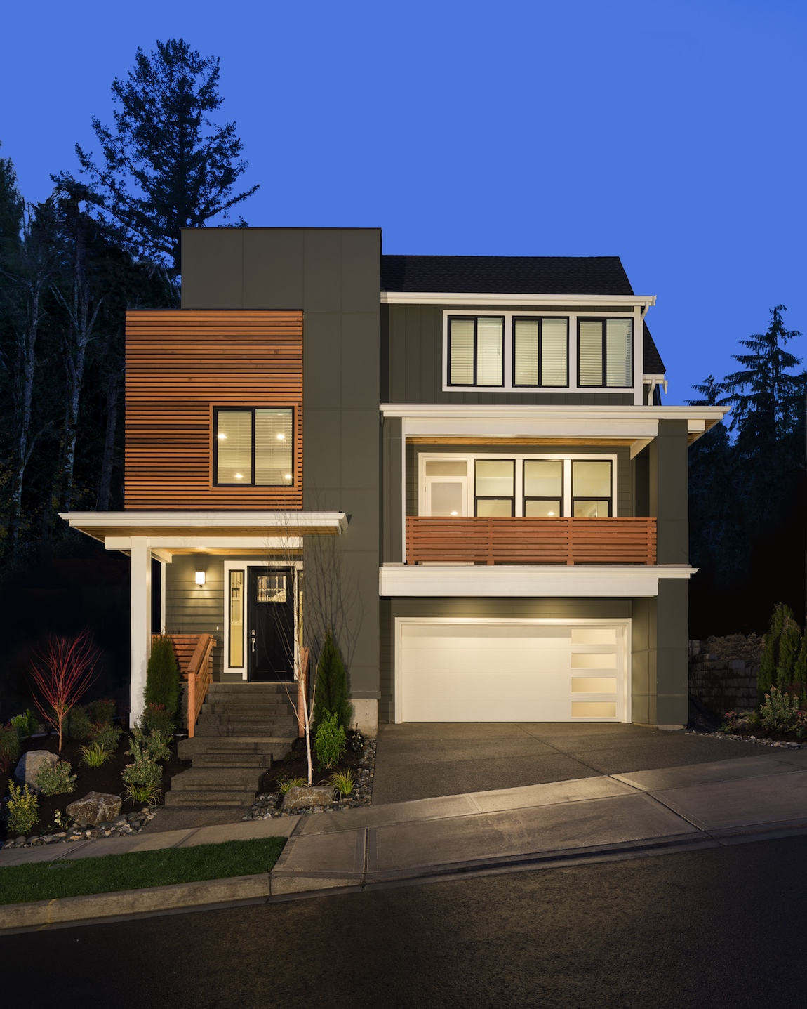 A modern design home with a dark green exterior and natural wood shiplap.