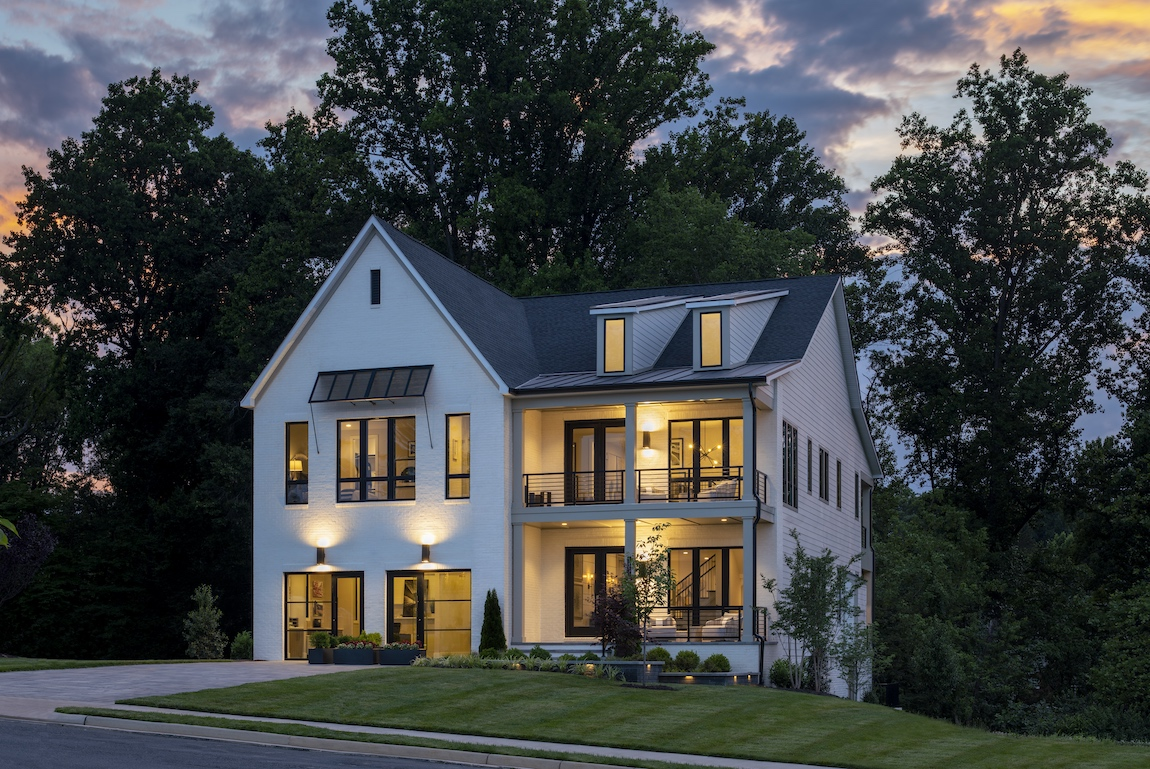 Toll Brothers model home in Virginia with lights on at dusk.