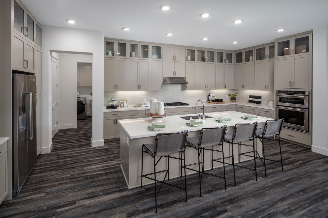 A luxury kitchen with lots of cabinets and a large island with seating.