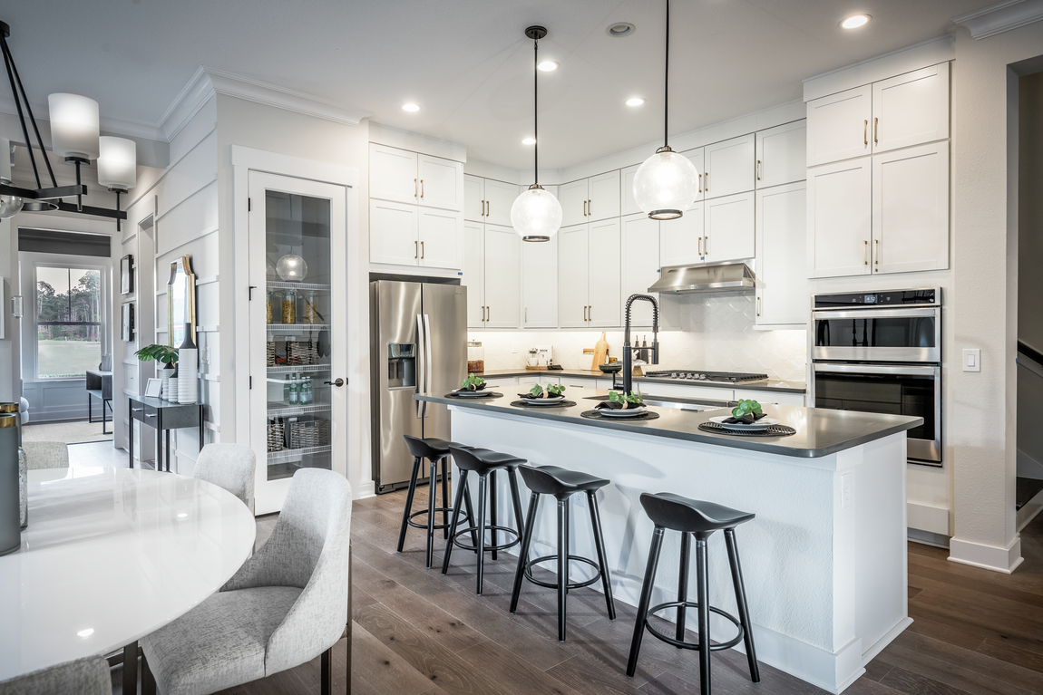 Luxury kitchen with white cabinets and four barstools along a tall kitchen island.