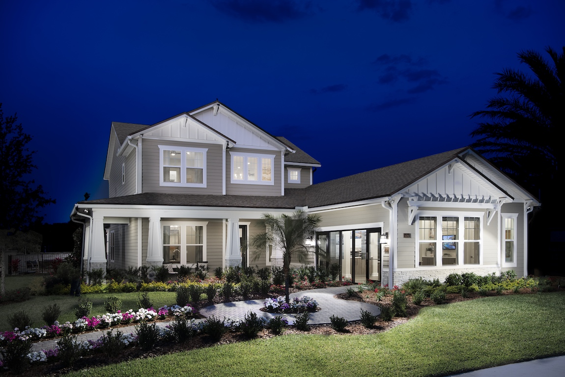 New construction home in Florida with lighting brightening the front yard.