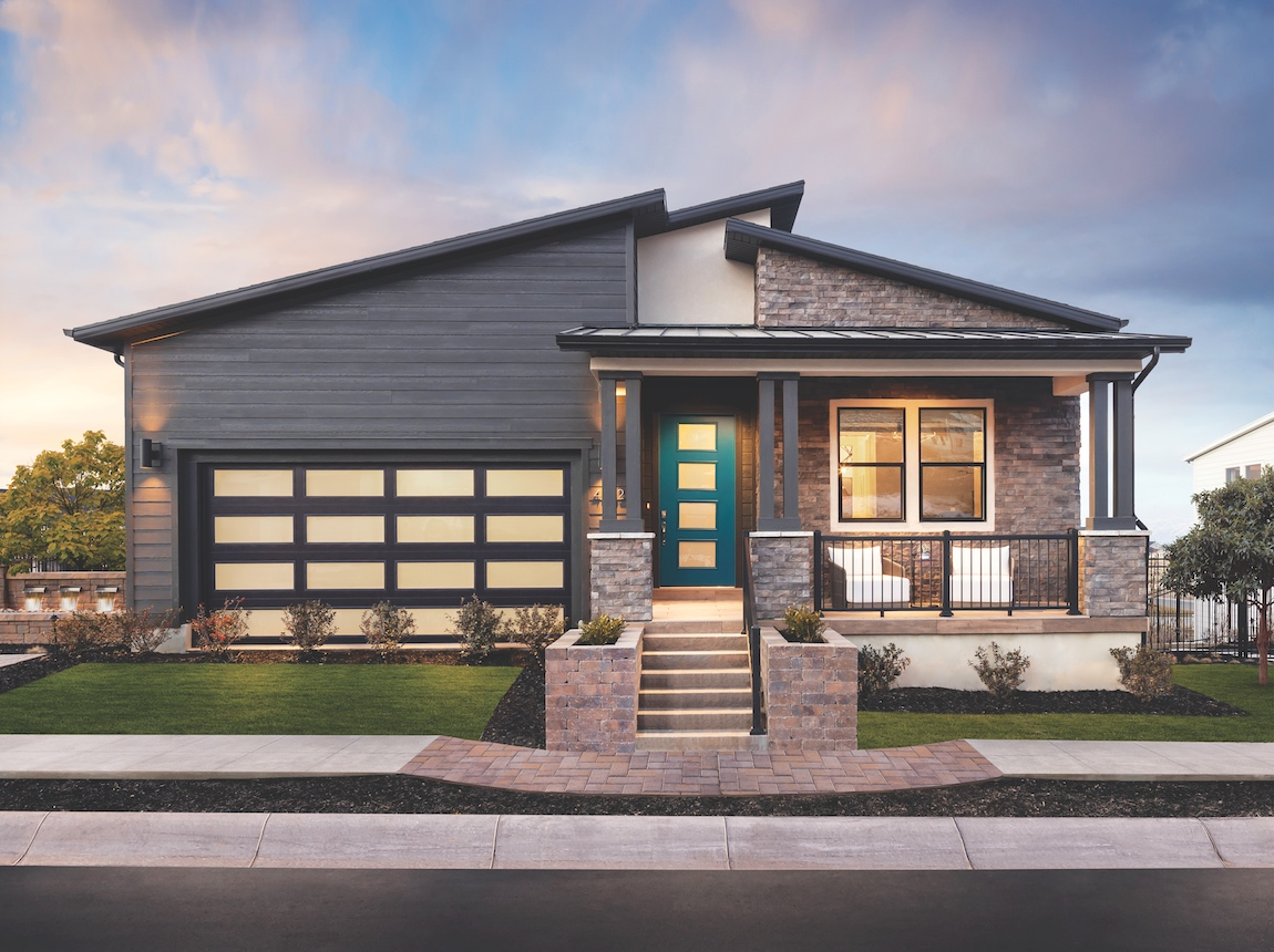 A contemporary Toll Brothers home with a bright turquoise exterior door.