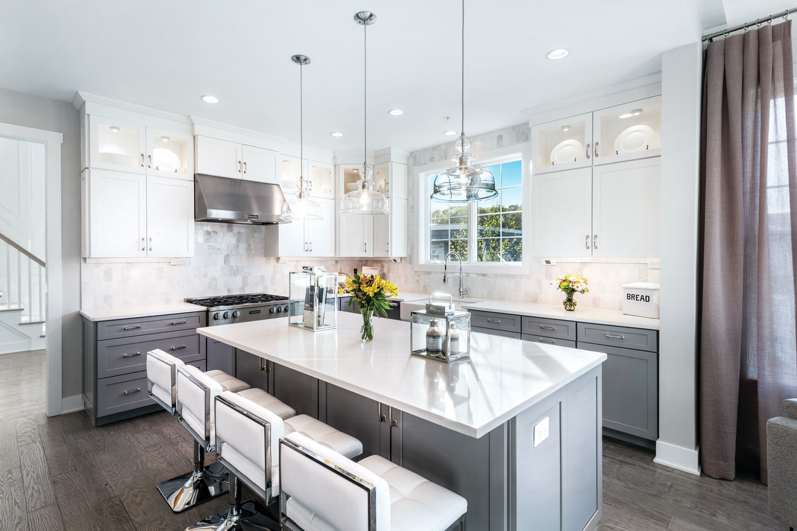 modern kitchen highlighted by pendant lighting and waterfall island