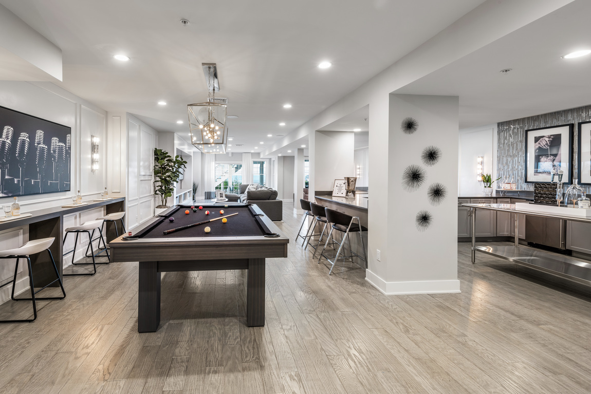 Luxe basement design with ample features such as pool table, home bar, and entertainment area