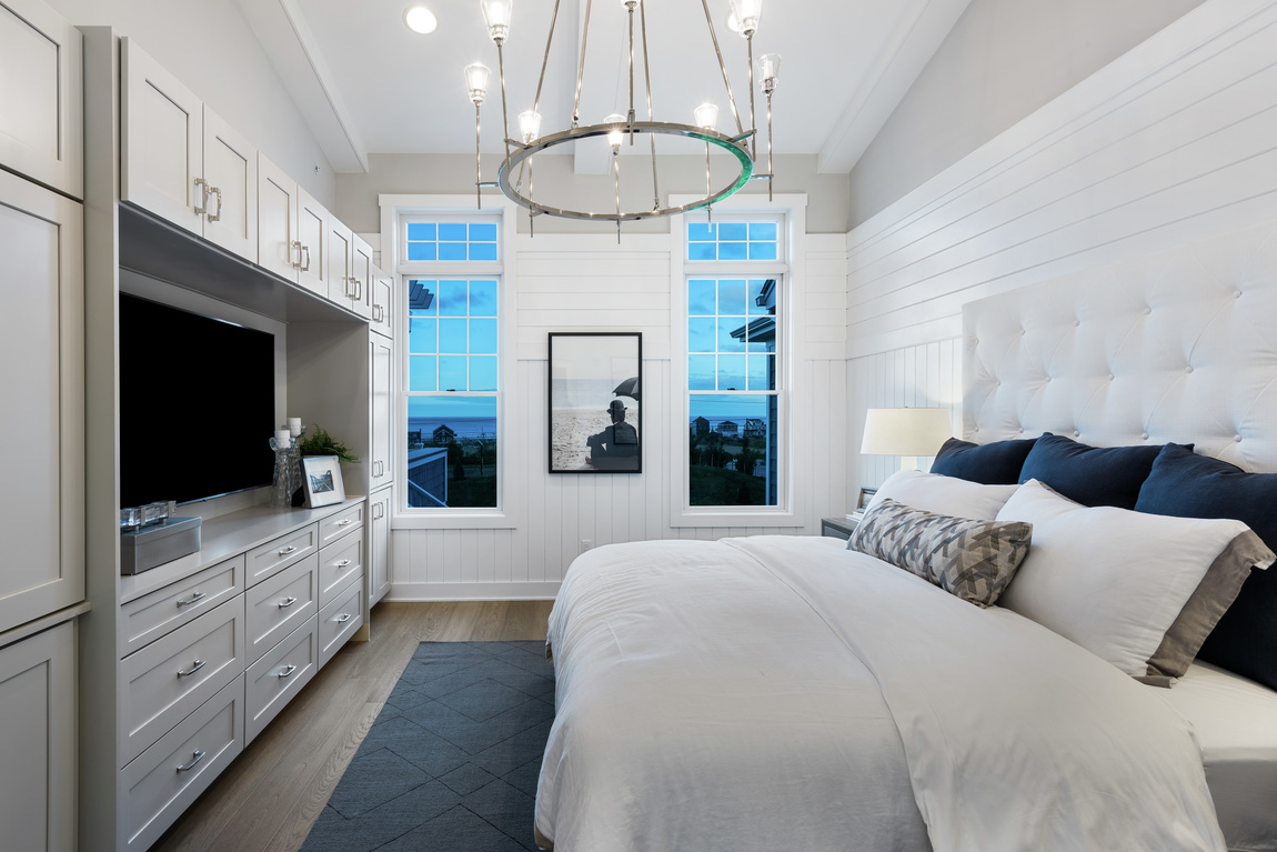 A luxury bedroom with white shiplap walls and white cabinets.