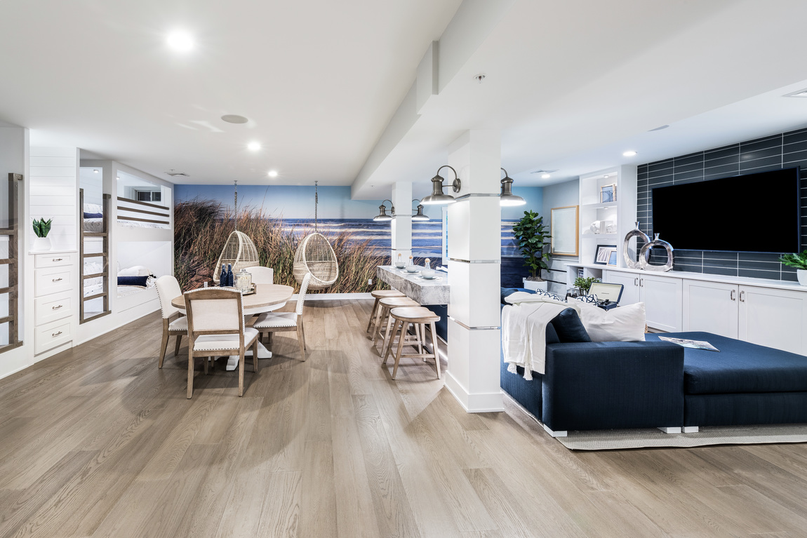 Well-furnished basement featuring artistic wallpaper that ties into home setting