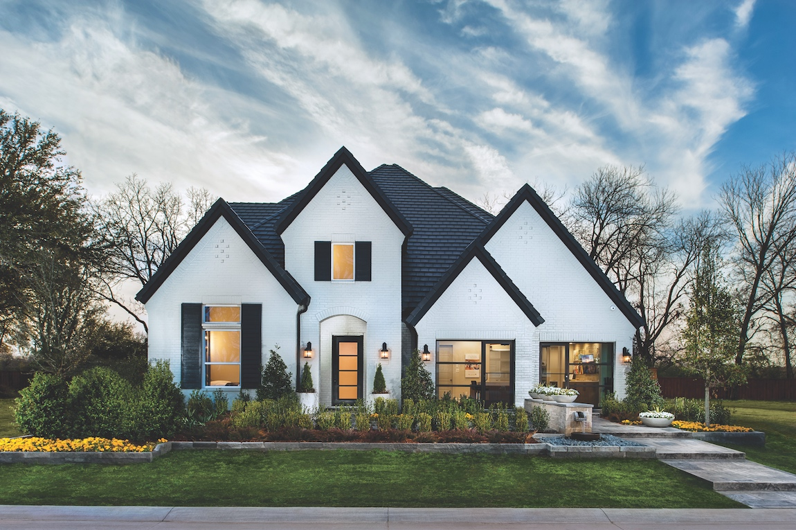 A Toll Brothers home in Texas with a white painted brick and dark trim exterior.