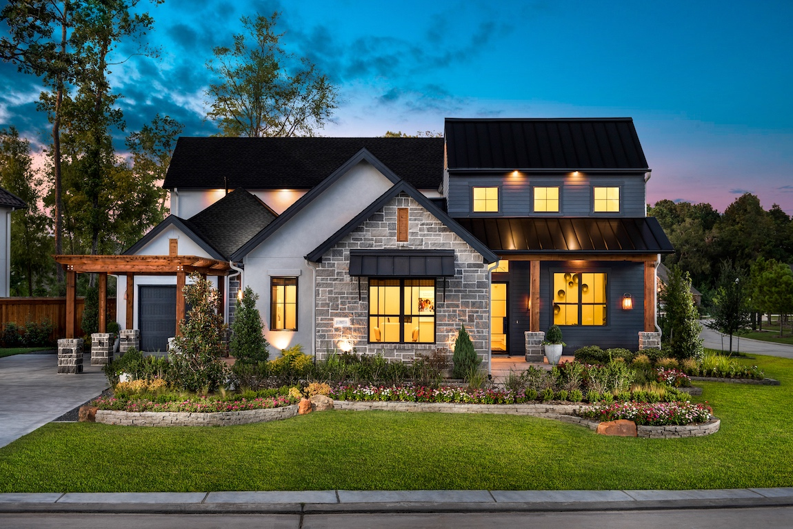 A modern farmhouse home in Texas with various exterior lighting.