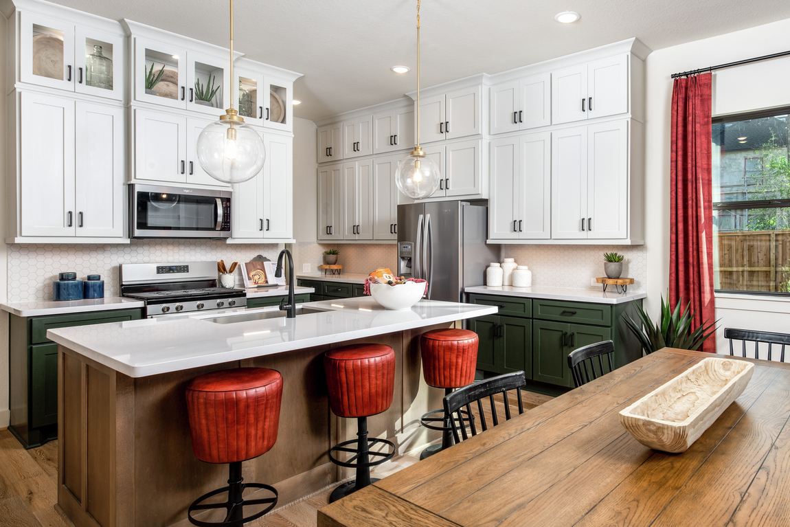 Kitchen featuring cherry-red barstools and a wooden kitchen island.