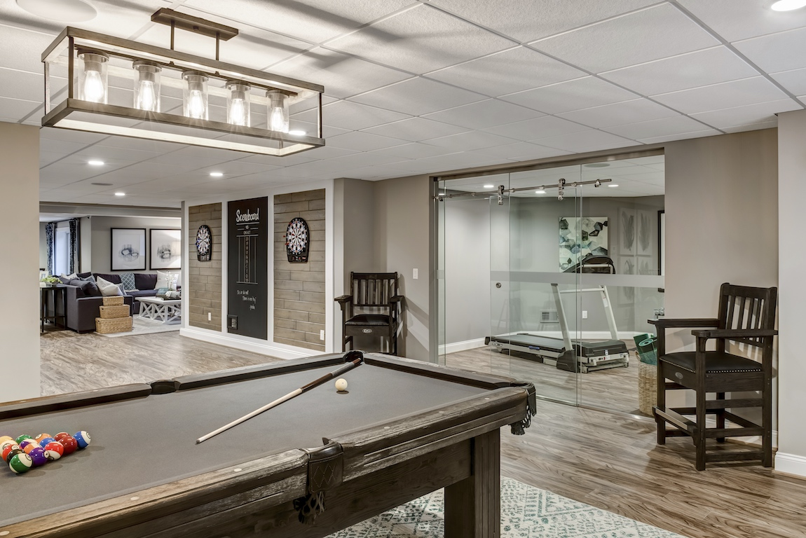 Modern glass barn door separating a home gym in a finished basement.