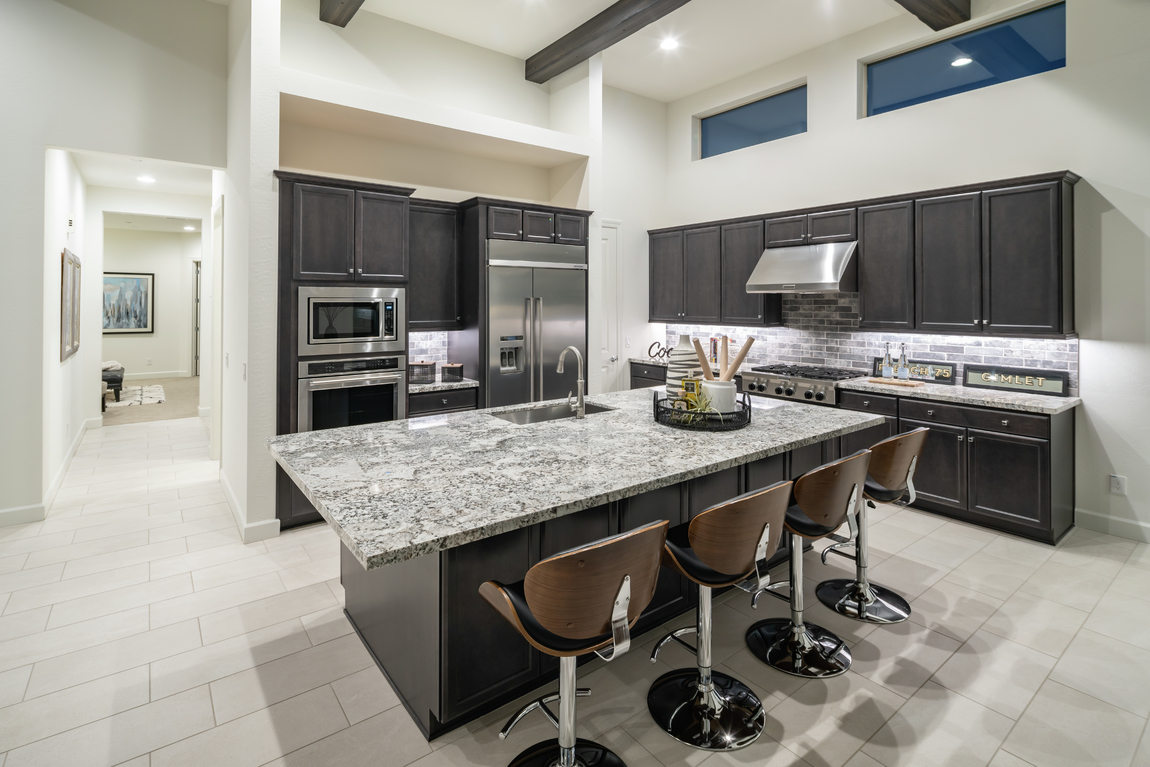 Kitchen featuring black cabinetry and gray backsplash