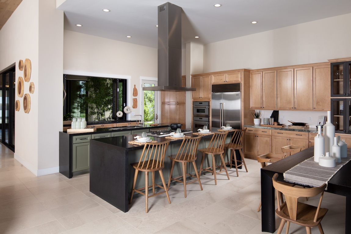 A large kitchen with a large center island that includes a black waterfall countertop.