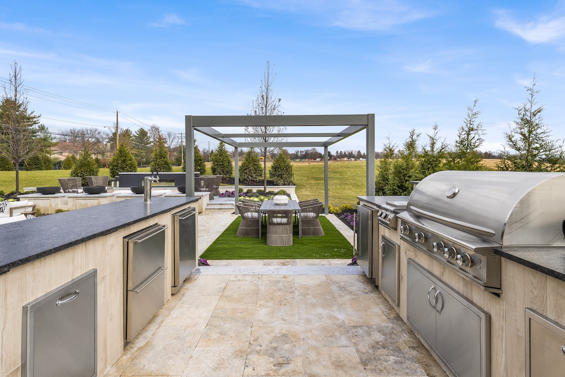 Luxurious backyard with a grill, countertops and sink for outdoor cooking.
