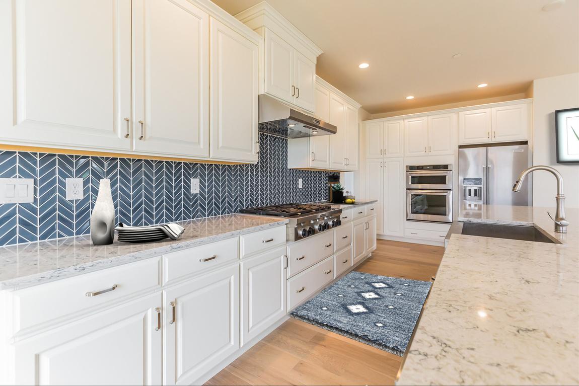 luxe kitchen with blue herringbone backsplash