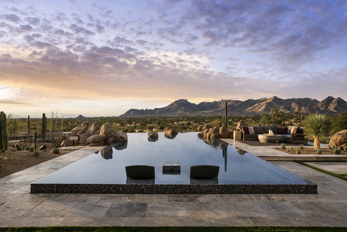 A luxury backyard pool in Arizona with a view of the desert and mountains.