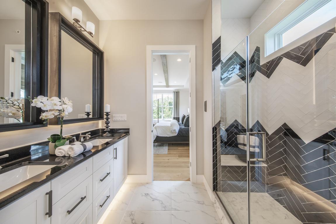 A modern bathroom with toe-kick and mirror lighting.