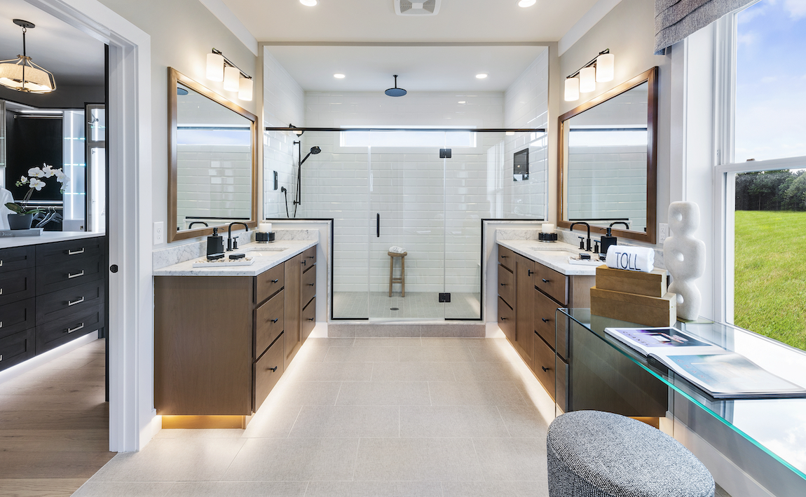 A luxury bathroom with a modern farmhouse aesthetic and wooden cabinets.