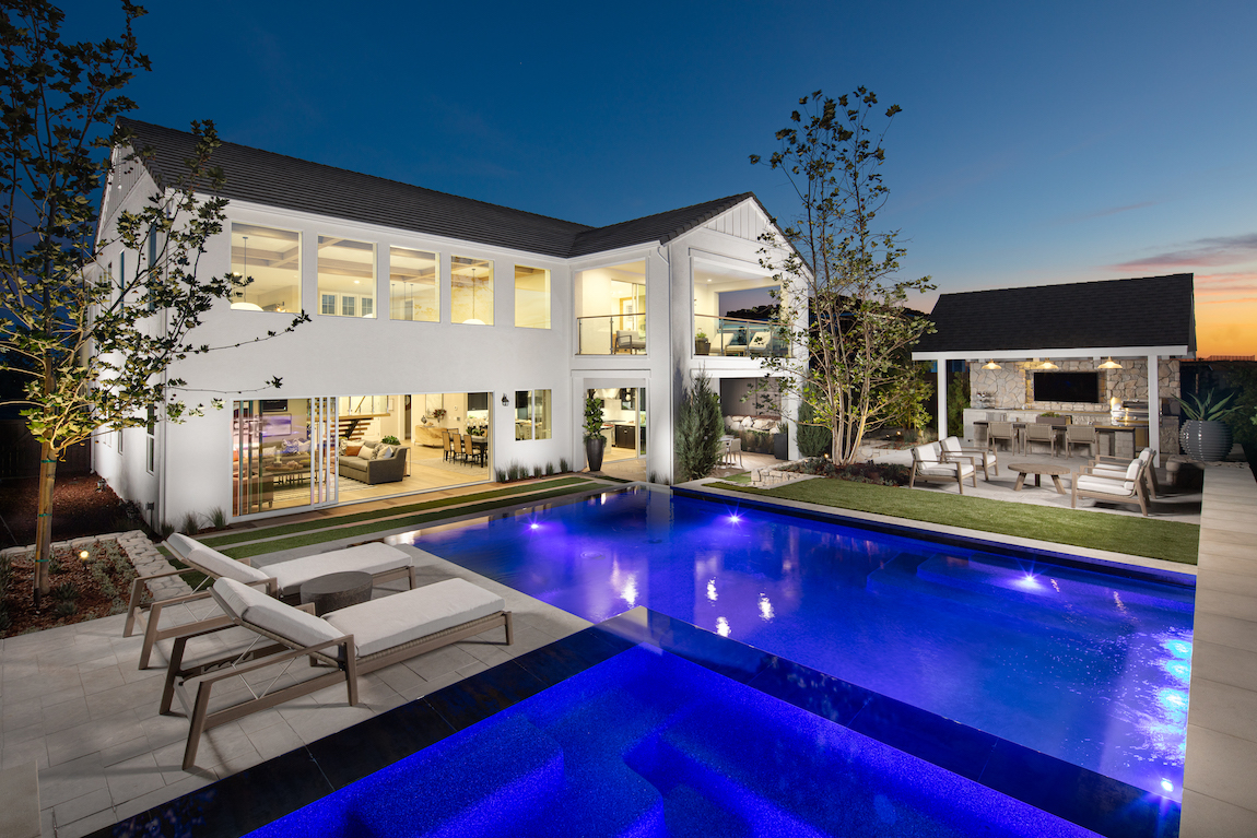 A modern farmhouse home with a backyard pool near a large sliding door that opens to the great room.