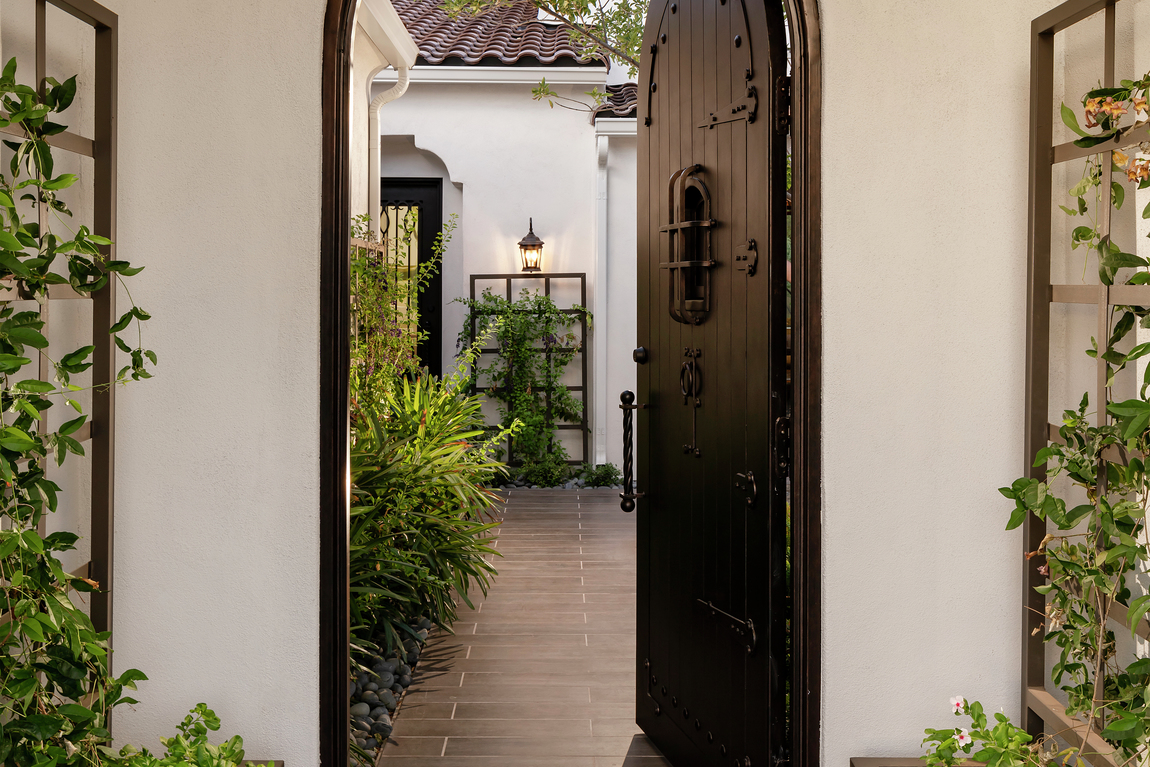 Black wooden door highlighted by subtle accents and arched framing