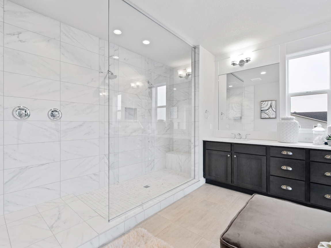 A large frameless shower in a luxury new construction bathroom.