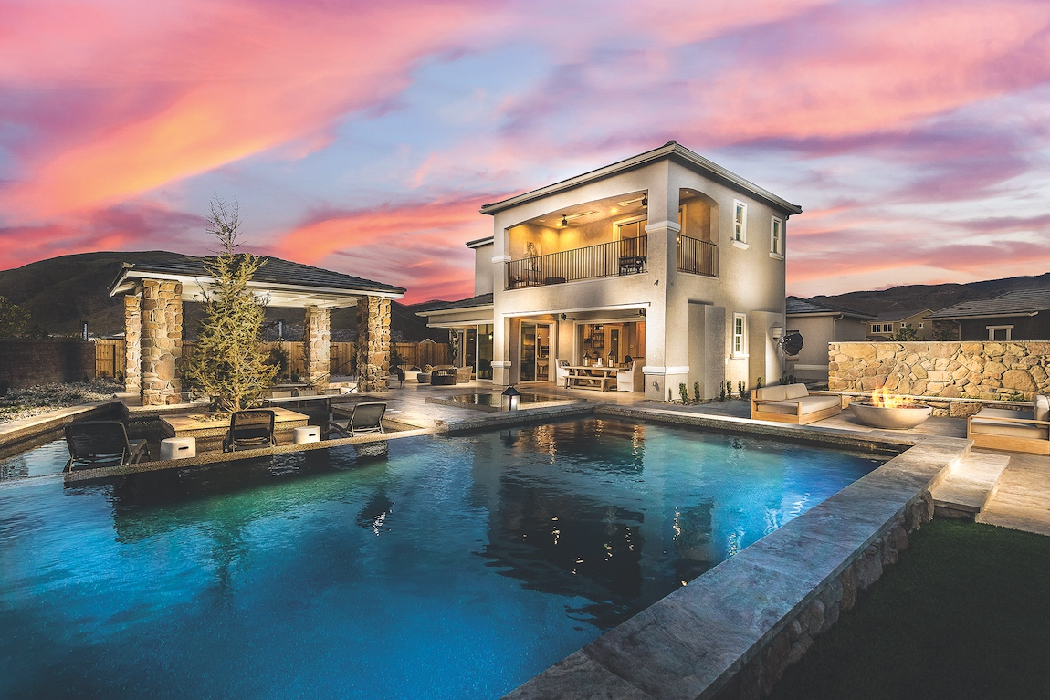 The back of a large luxury house in Reno at dusk with a lit up pool and outdoor living area.