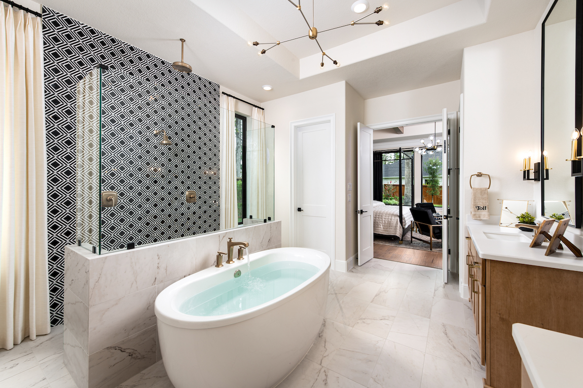 A luxury bathroom with a free-standing bathtub, an accent wall and gold fixtures.