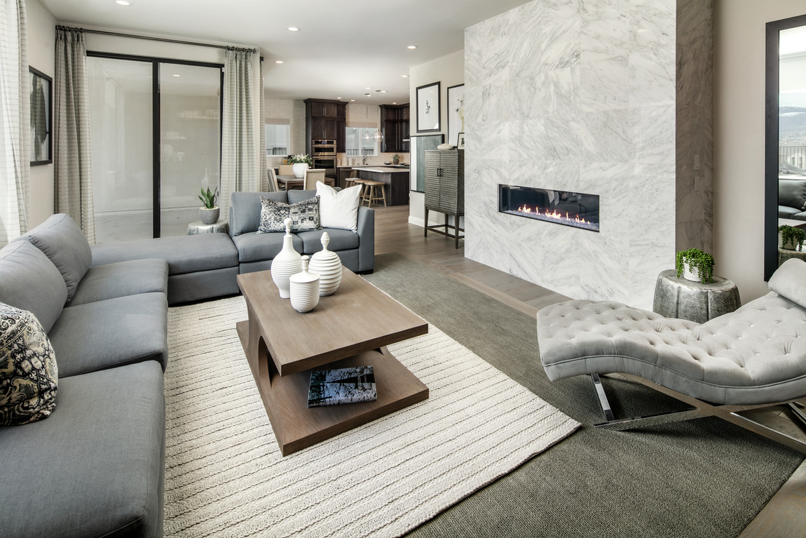A living room with a linear fireplace built into tile wall.