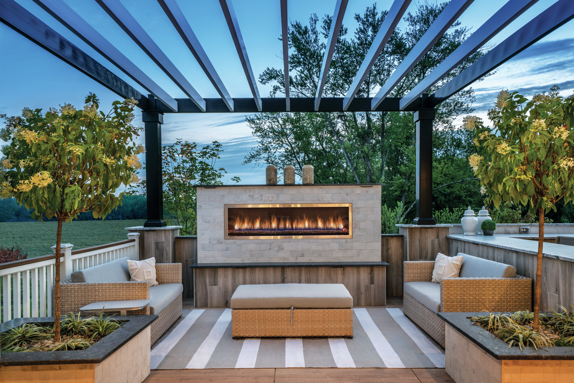An outdoor patio with a large outdoor fireplace.