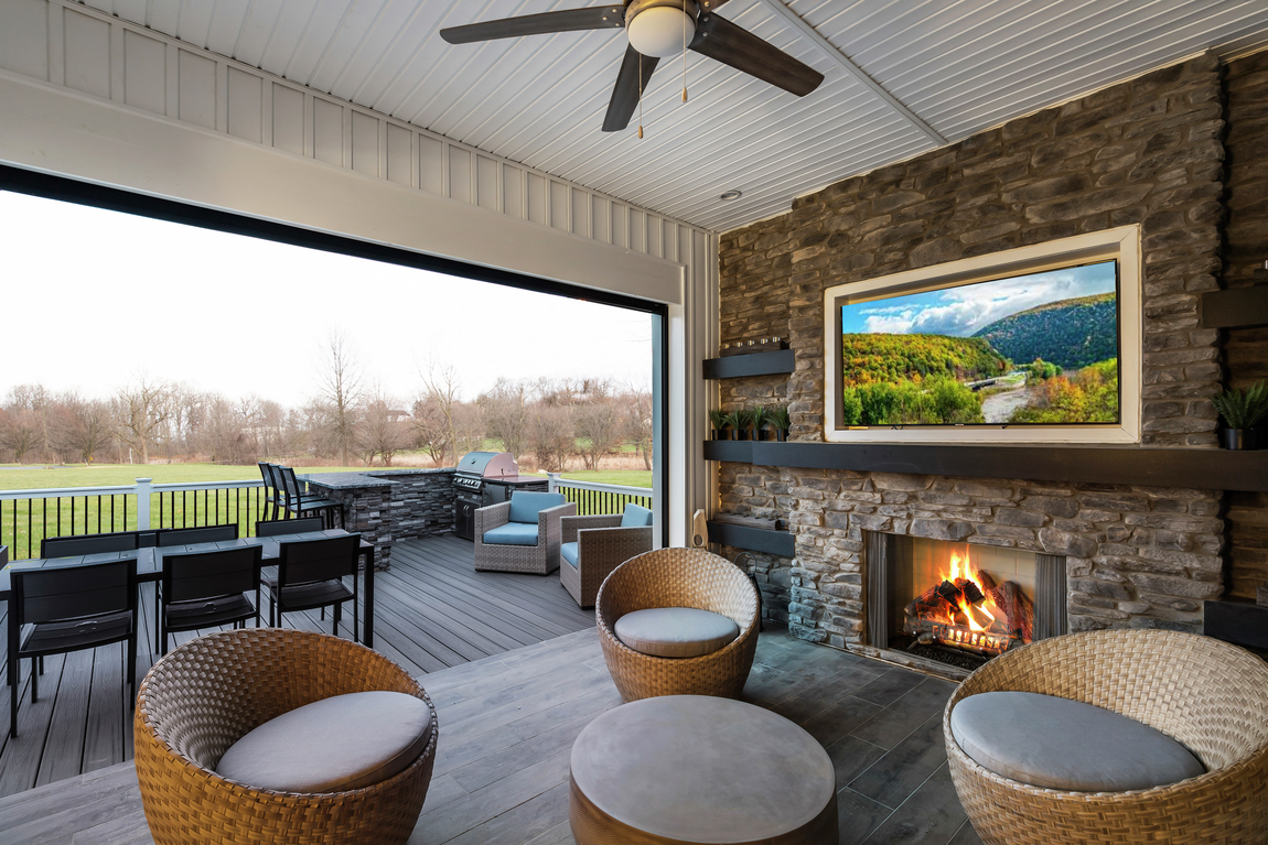 A patio with a TV, and seats overlooking an open field.