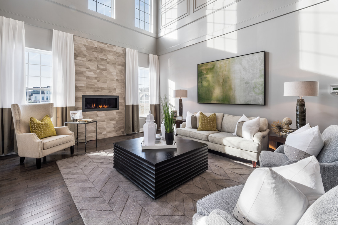 A large living room lots of natural windows and a ledge stone fireplace.