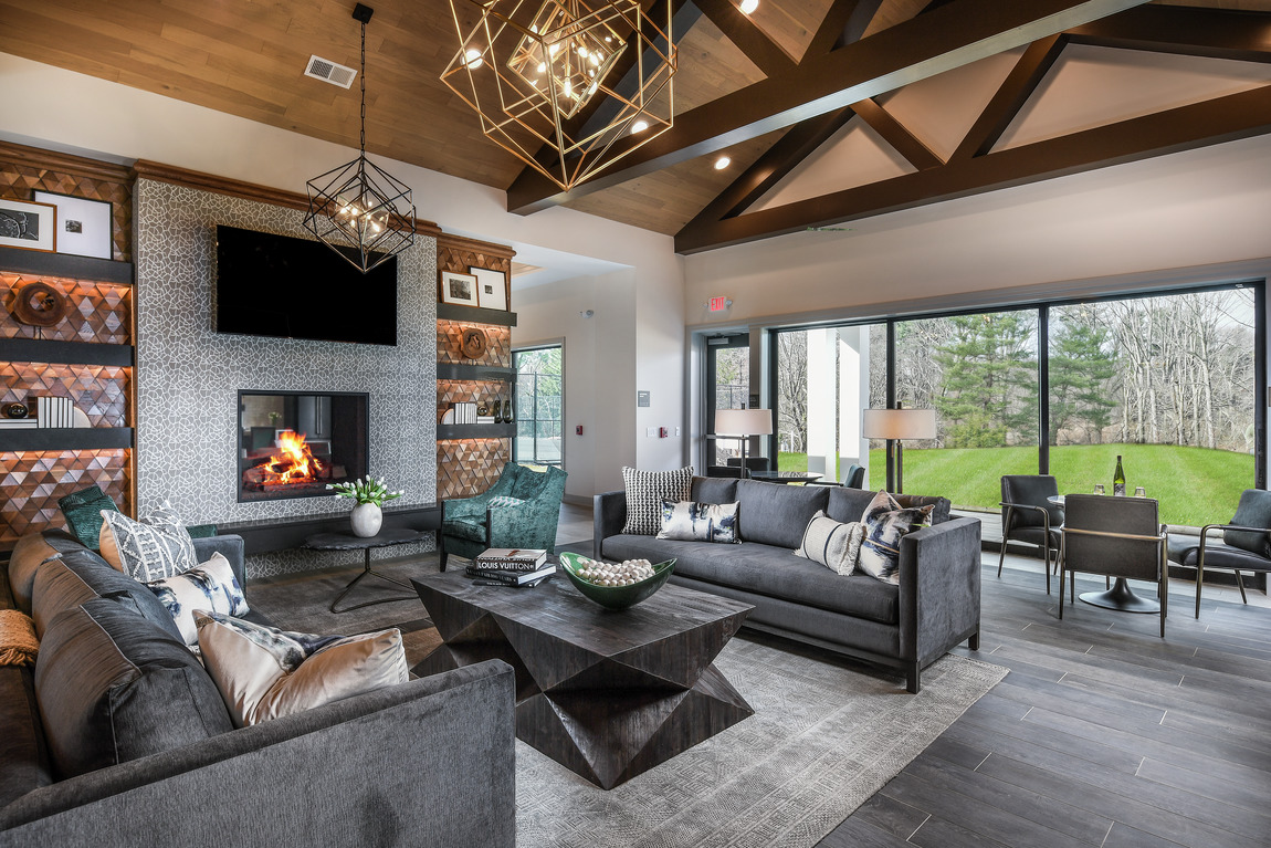 A great room with a large fireplace surrounded by textured tile.