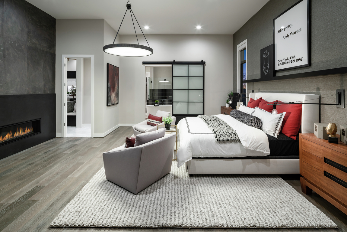 A large bedroom with a modern glass barn door and a fireplace place in front of the bed.