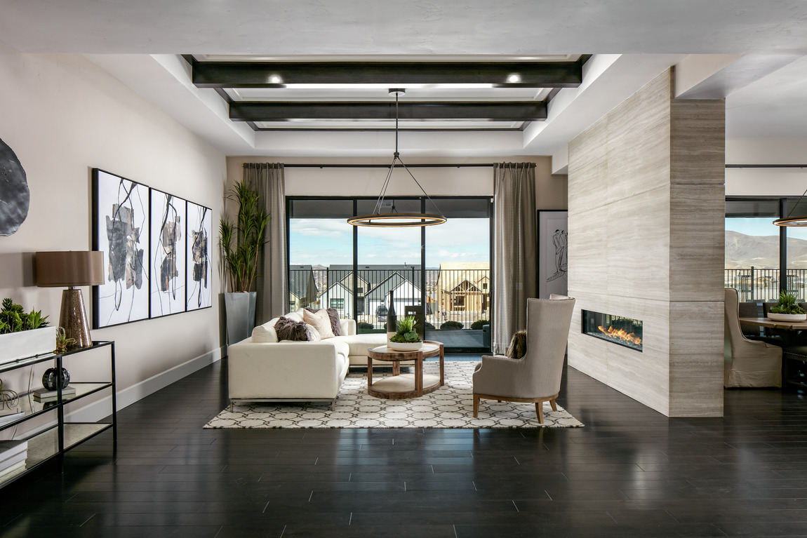 Open concept home with a dual-sided fireplace dividing two spaces.