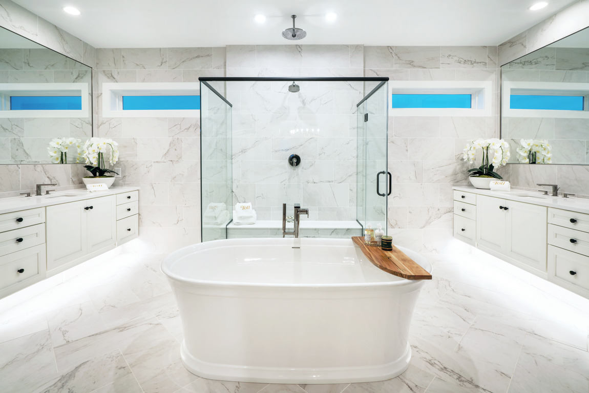 Luxury bathroom with a glass shower and toe kick lighting under cabinets.