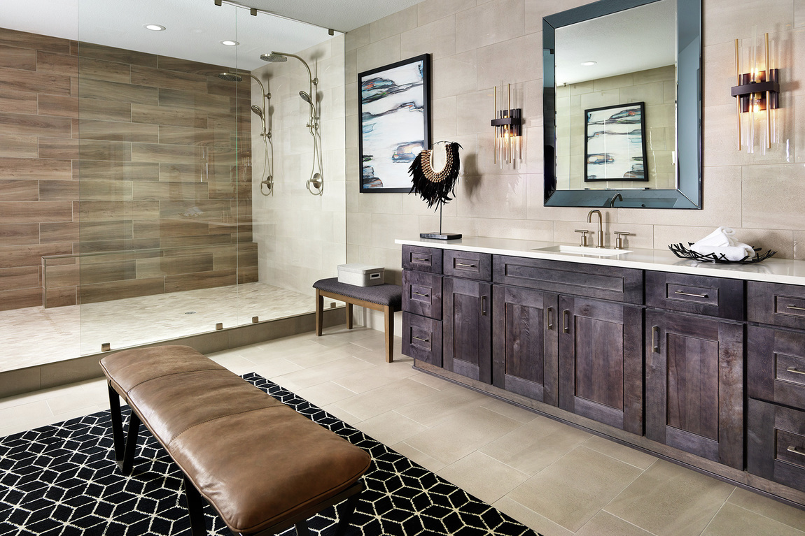 Large primary bathroom with an accent wall in a walk-in shower and brown cabinets.