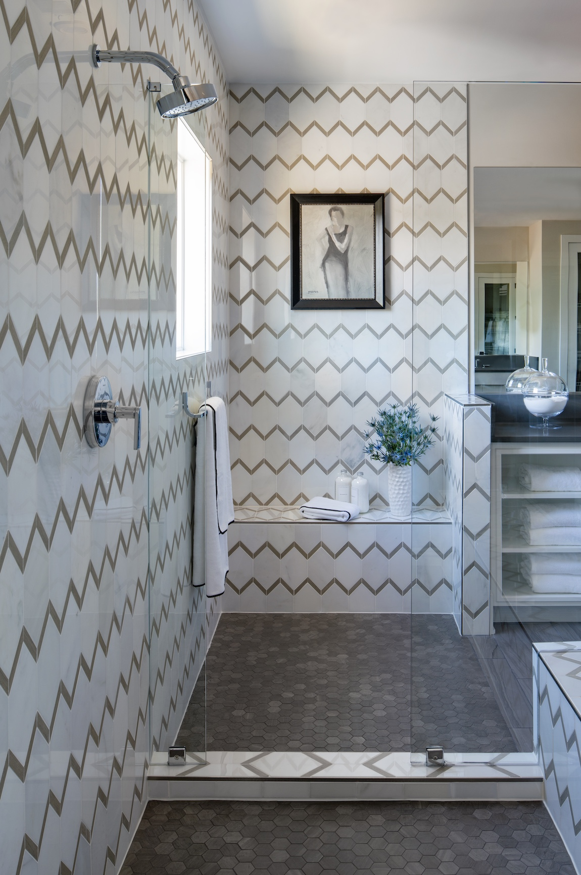 Walk-in shower a seat and a patterned tile.