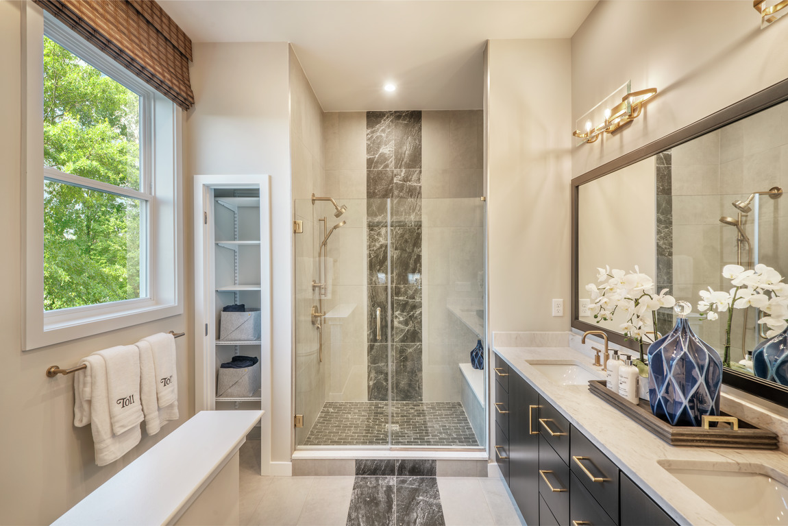 Luxury primary bathroom with gold accents and tiles floor and walls.